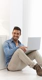 Happy young man browsing internet at home Royalty Free Stock Photo