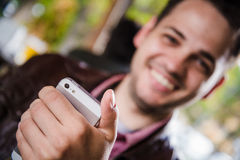 Happy young man browsing internet on smartphone sitting at outdoor cafe. Selective focus. Happy young man browsing internet on smartphone sitting at outdoor Royalty Free Stock Image