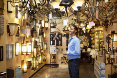 Happy young man browsing for lights fixture in store Royalty Free Stock Image