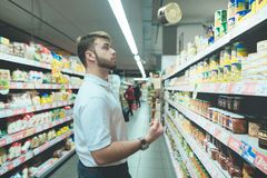 A beautiful man chooses canned food from supermarket shelves. A man with a beard juggles the goods in the store. Happy young man buying tinned food at grocery Stock Photos