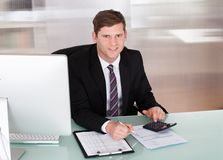 Happy young man calculating finances Stock Images