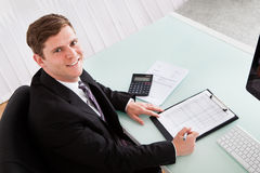 Happy young man calculating finances Royalty Free Stock Photo