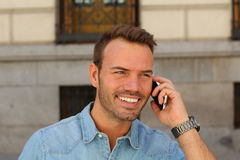 Happy young man calling with mobile phone . He is calling somebody by mobile telephone on the street Stock Images