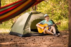 Happy young man camping and strum a guitar instrumental music to relax against background of forest sunset. royalty free stock images