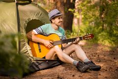 Happy young man camping and strum a guitar instrumental music to relax against background of forest sunset. stock photo