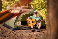 Happy young man camping and strum a guitar instrumental music to relax against background of forest sunset. Wilderness Travel stock photo