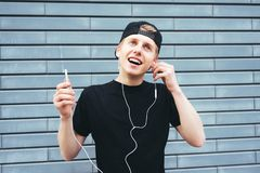 Happy young man in a cap and a black T-shirt enjoys listening to music. Student listening to music on a background of blue wall Stock Photos