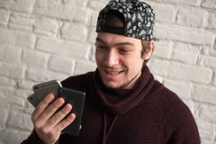 Happy young man in a cap and sweater holding three smartphones in his hand and look at them Stock Image