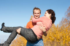 Happy young man carries his wife in arms Royalty Free Stock Image