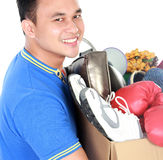 Happy young man carrying box full of stuff Stock Photography