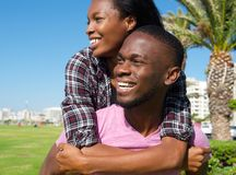 Happy young man carrying girlfriend on back Stock Photo