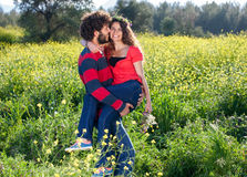 Happy young man carrying his beautiful girlfriend. Royalty Free Stock Image