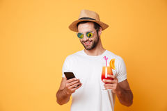 Happy young man chatting by mobile phone holding cocktail. Picture of happy young man standing isolated over yellow background. Looking aside chatting by mobile Stock Photo