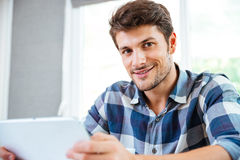 Happy young man in checkered shirt using tablet at home Stock Photography