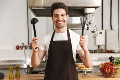 Happy young man chef cook in apron standing. At the kitchen, holding ladle and whisk stock photos