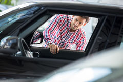 Happy young man chooses to buy a car. At the car dealership saloon Stock Photography