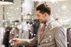 Happy young man choosing bow-tie in clothing store Royalty Free Stock Images