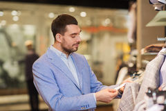 Happy young man choosing clothes in clothing store. Sale, shopping, fashion, style and people concept - elegant young man in jacket choosing clothes and looking Royalty Free Stock Photo