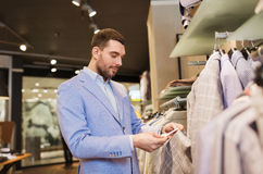 Happy young man choosing clothes in clothing store. Sale, shopping, fashion, style and people concept - elegant young man in jacket choosing clothes and looking Royalty Free Stock Photography