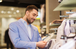 Happy young man choosing clothes in clothing store. Sale, shopping, fashion, style and people concept - elegant young man in jacket choosing clothes and looking Stock Images