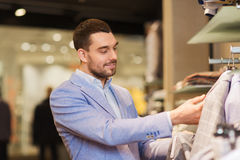 Happy young man choosing clothes in clothing store. Sale, shopping, fashion, style and people concept - elegant young man in jacket choosing clothes in mall or Royalty Free Stock Image