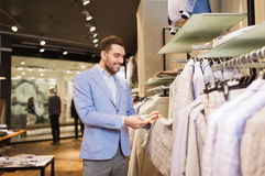 Happy young man choosing clothes in clothing store. Sale, shopping, fashion, style and people concept - elegant young man in jacket choosing clothes in mall or Royalty Free Stock Photos