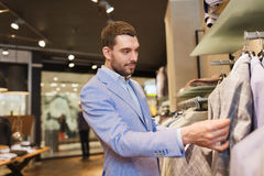 Happy young man choosing clothes in clothing store. Sale, shopping, fashion, style and people concept - elegant young man in jacket choosing clothes in mall or Royalty Free Stock Images