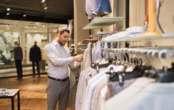 Happy young man choosing clothes in clothing store. Sale, shopping, fashion, style and people concept - elegant young man choosing clothes in mall or clothing Royalty Free Stock Image