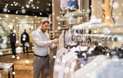Happy young man choosing clothes in clothing store. Sale, shopping, fashion, style and people concept - elegant young man choosing clothes in mall or clothing Royalty Free Stock Photo