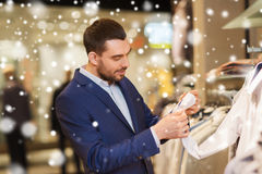 Happy young man choosing clothes in clothing store. Sale, shopping, fashion, style and people concept - elegant young men in suit choosing clothes in mall or Stock Images
