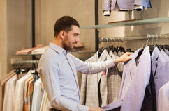 Happy young man choosing clothes in clothing store Stock Photo