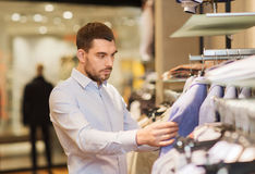Happy young man choosing clothes in clothing store Stock Image