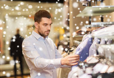 Happy young man choosing clothes in clothing store. Sale, shopping, fashion, style and people concept - elegant young man in shirt choosing clothes in mall or Royalty Free Stock Photos
