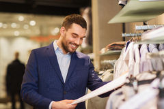 Happy young man choosing clothes in clothing store. Sale, shopping, fashion, style and people concept - happy elegant young man in suit choosing clothes in mall Royalty Free Stock Photography