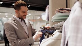 Happy young man choosing clothes in clothing store stock video