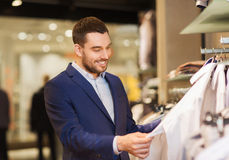 Happy young man choosing clothes in clothing store. Sale, shopping, fashion, style and people concept - elegant young man in suit choosing clothes in mall or Stock Photo