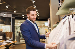 Happy young man choosing clothes in clothing store. Sale, shopping, fashion, style and people concept - elegant young man in suit choosing clothes in mall or Stock Images