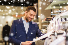 Happy young man choosing clothes in clothing store. Sale, shopping, fashion, style and people concept - happy elegant young man in suit choosing clothes in mall Stock Photo