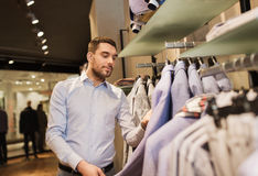 Happy young man choosing clothes in clothing store. Sale, shopping, fashion, style and people concept - happy young man in shirt choosing jacket in mall or Stock Photo