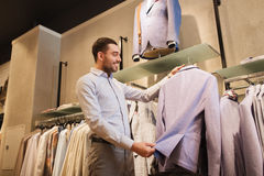 Happy young man choosing clothes in clothing store. Sale, shopping, fashion, style and people concept - happy young man in shirt choosing jacket in mall or Stock Image