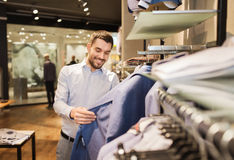 Happy young man choosing clothes in clothing store. Sale, shopping, fashion, style and people concept - happy young man in shirt choosing jacket in mall or Royalty Free Stock Photo