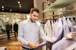 Happy young man choosing clothes in clothing store. Sale, shopping, fashion, style and people concept - happy young man in shirt choosing jacket in mall or Royalty Free Stock Images
