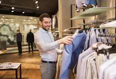 Happy young man choosing clothes in clothing store. Sale, shopping, fashion, style and people concept - happy young man in shirt choosing jacket in mall or Royalty Free Stock Photography