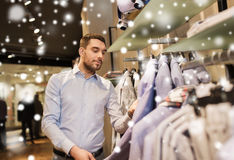 Happy young man choosing clothes in clothing store Royalty Free Stock Images