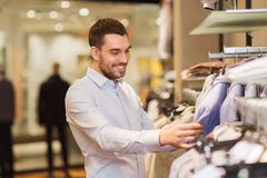 Happy young man choosing clothes in clothing store. Sale, shopping, fashion, style and people concept - happy young man in shirt choosing clothes in mall or Royalty Free Stock Photos