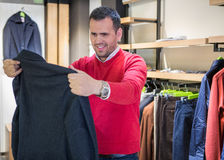 Happy young man choosing jacket in mall or clothing store. Stock Images