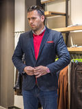 Happy young man choosing jacket in mall or clothing store. sale, Stock Photos