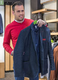 Happy young man choosing jacket in mall or clothing store. sale, Royalty Free Stock Photo