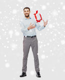 Happy young man with christmas gift box over snow Stock Image