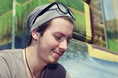 Happy Young man in the city. Sitting in front of colorful wall. Selective focus Stock Image